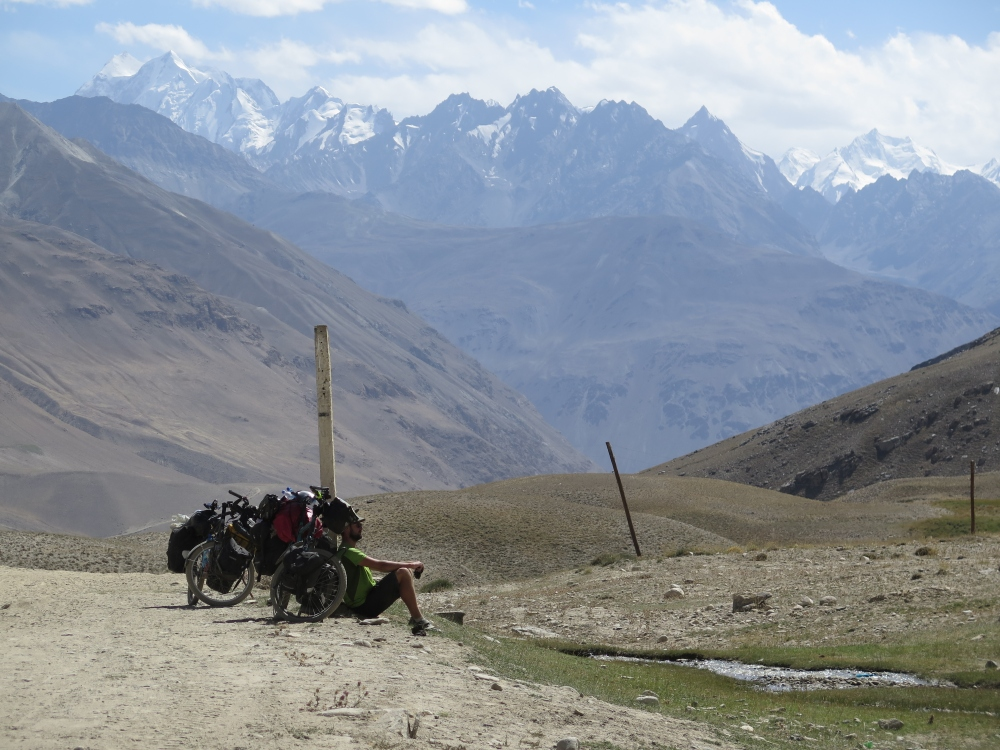 A little exhausted after pushing my bike through miles of sand, while the sight of the Hindu Kush in the background makes everything OK. Photo courtesy of Hubert.